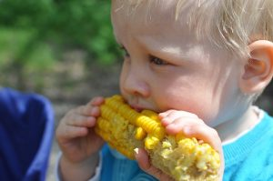 child eating salted corn